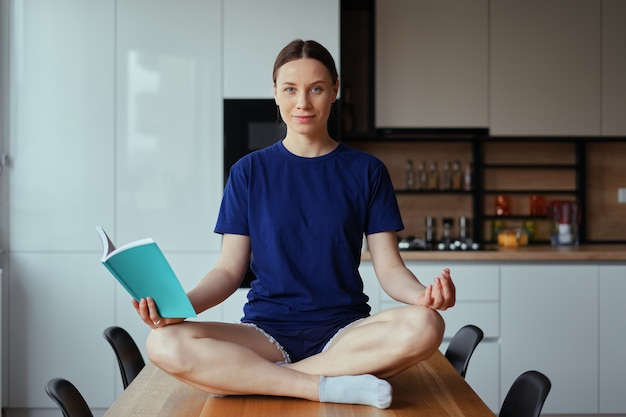 Schöne frau, die auf tisch in yoga-posen liest