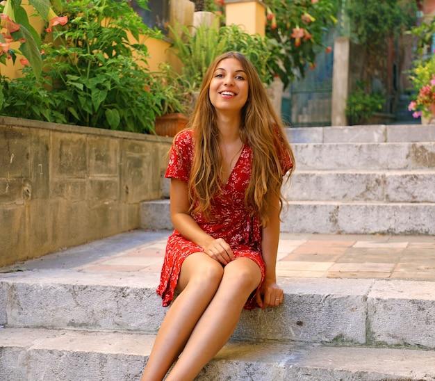 Schöne frau, die auf treppen im dorf taormina in sizilien, italien sitzt