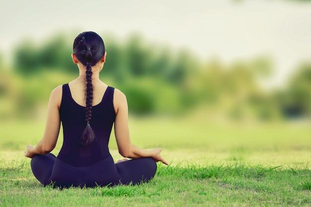 Schöne frau, die auf yogalagen für eine ausgeglichene übung des körpers sitzt.