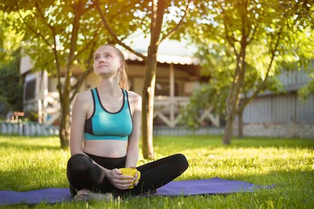 Schöne frau, die auf yogamatte mit tasse tee sitzt.