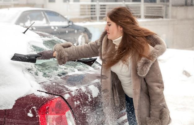 Schöne frau, die auto bei blizzard säubert