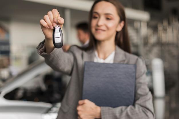 Schöne frau, die autoschlüssel hält