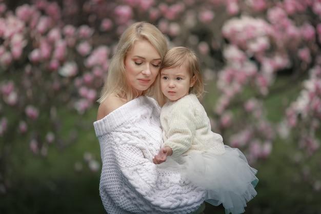 Schöne frau, die baby auf hintergrund des blühenden baumes mit roten blumen hält