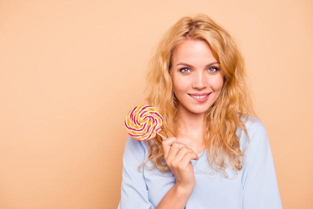 Schöne frau, die beim halten der süßigkeit aufwirft