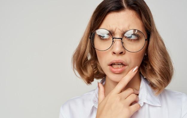 Schöne frau, die brille kurzes haar weißes hemd beige trägt.