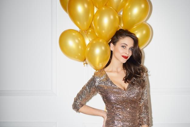 Schöne frau, die bündel der goldenen luftballons hält