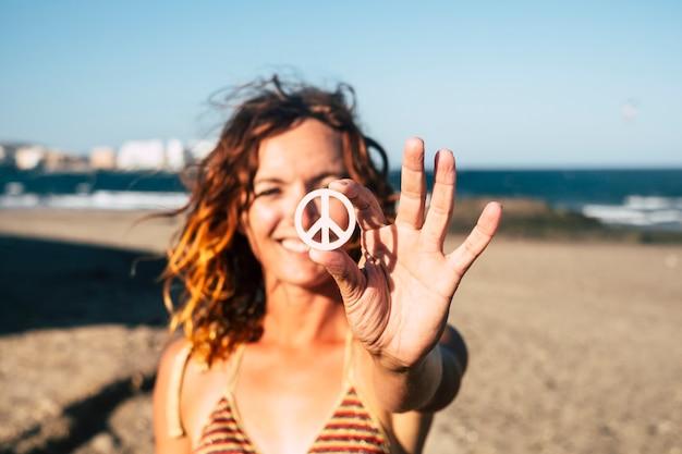 Schöne frau, die das symbol des friedens allein am strand zeigt und isoliert mit dem meer und dem sand des strandes im hintergrund - kaukasisches mädchen, das lächelt und in die kamera schaut