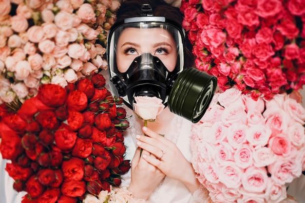 Schöne frau, die den duft von blumen in der gasmaske genießt und riecht. allergie-schutz-apothekenkonzept.