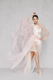 Schöne frau, die den saum des transparenten kleides wirft