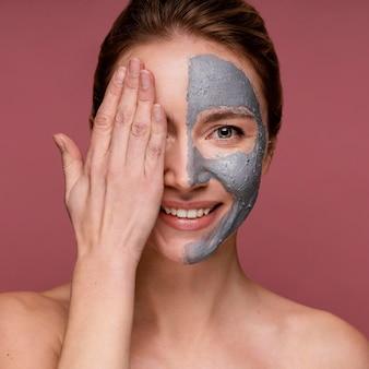 Schöne frau, die die hälfte ihres gesichts mit maske bedeckt