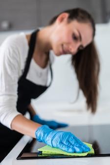Schöne frau, die die hausarbeit beim reinigen in der küche tut