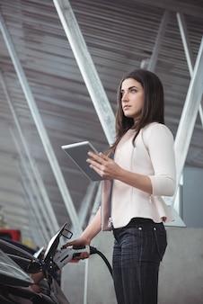 Schöne frau, die digitales tablett beim laden des elektroautos verwendet