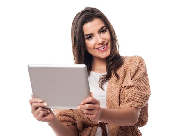 Schöne frau, die digitales tablett hält