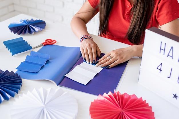Schöne frau, die diy-papierrosetten der roten und blauen farben macht, um 4. juli zu feiern