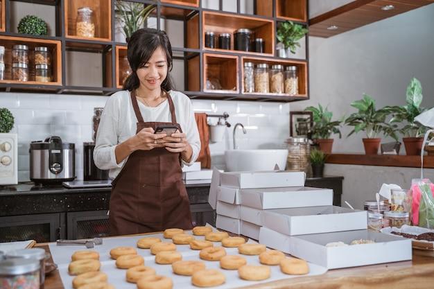 Schöne frau, die donuts in der küche vorbereitet
