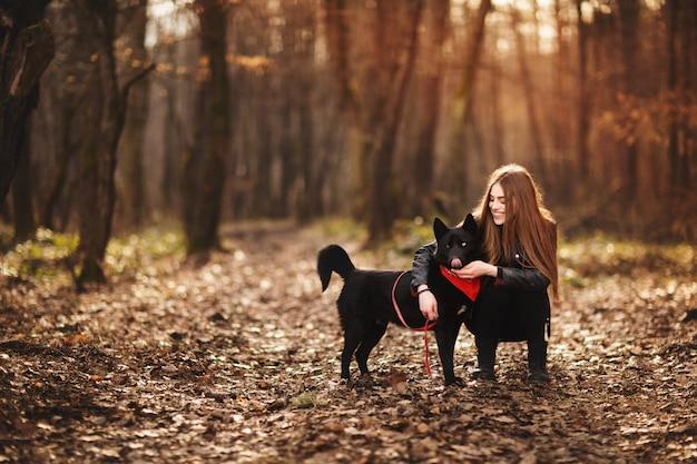 Schöne frau, die draußen ihren hund streicht