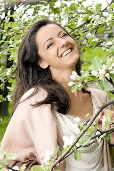 Schöne frau, die durch blühenden baum lacht