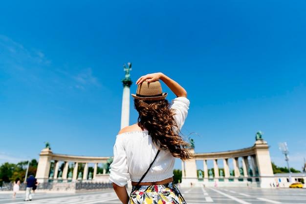 Schöne frau, die durch budapest - heldenplatz reist. tourismus-konzept.
