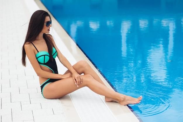 Schöne frau, die durch den pool ruht