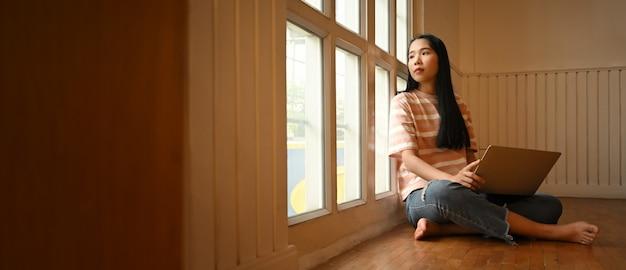 Schöne frau, die durch fenster schaut, während sie einen computer-laptop benutzt, der auf ihren schoß setzt und auf dem holzboden des wohnzimmers sitzt.