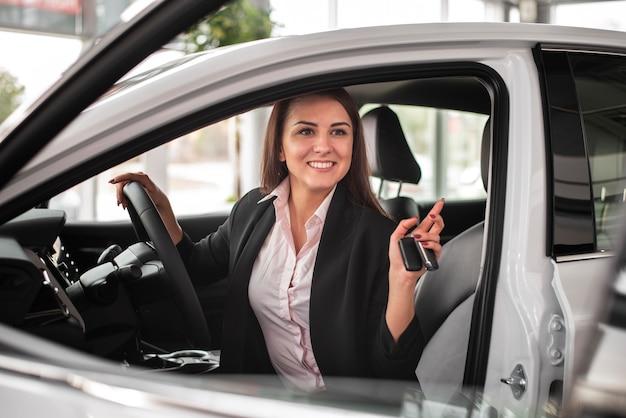 Schöne frau, die ein auto eine verkaufsstelle prüft