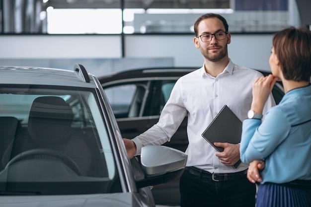 Schöne frau, die ein auto kauft