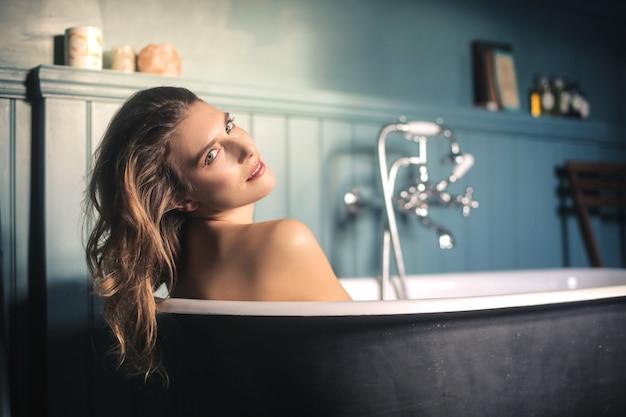 Schöne frau, die ein bad in einem eleganten antiken badezimmer hat