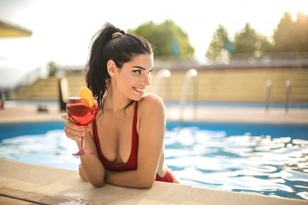 Schöne frau, die ein cocktail beim kühlen in einem swimmingpool trinkt