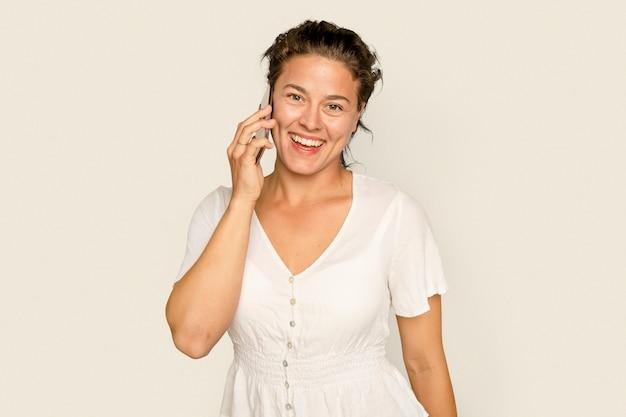 Schöne frau, die ein digitales gerät des telefonanrufs hat