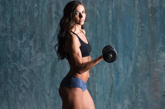 Schöne frau, die ein fitness-training mit gewichten auf einem dunklen hintergrund tut.