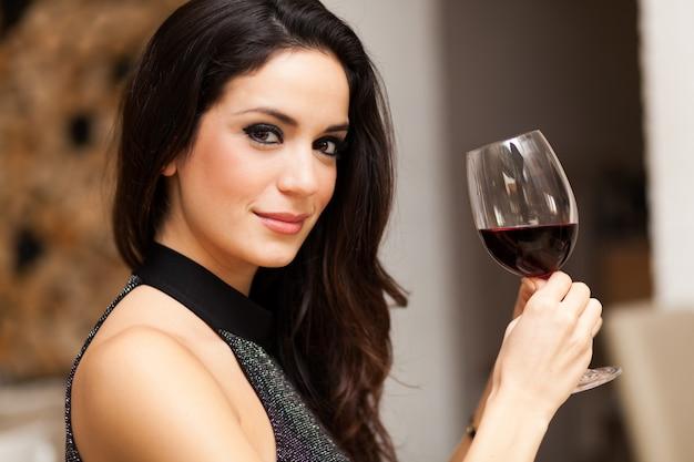Schöne frau, die ein glas rotwein anhält