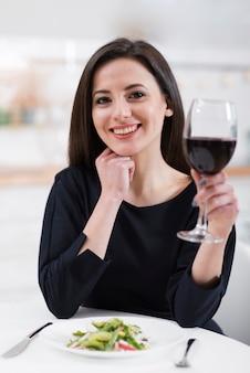 Schöne frau, die ein glas rotwein hält