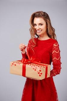 Schöne frau, die ein großes geschenk öffnet