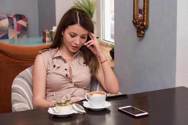 Schöne frau, die ein handy im café benutzt. e-book lesen