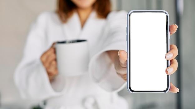 Schöne frau, die ein leeres telefon zeigt