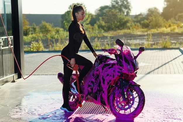 Schöne frau, die ein motorrad wäscht