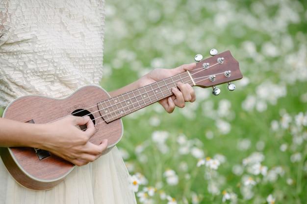 Schöne frau, die ein nettes weißes kleid trägt und eine ukulele anhält