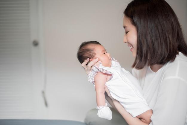 Schöne frau, die ein neugeborenes schätzchen in ihren armen anhält