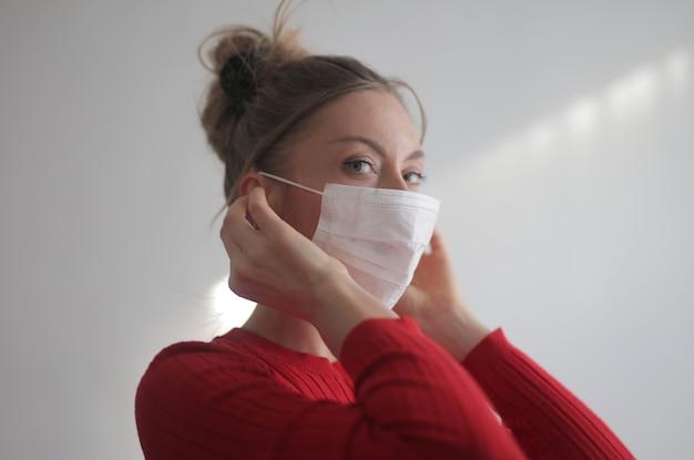Schöne frau, die ein rotes hemd und eine chirurgische maske auf weiß trägt