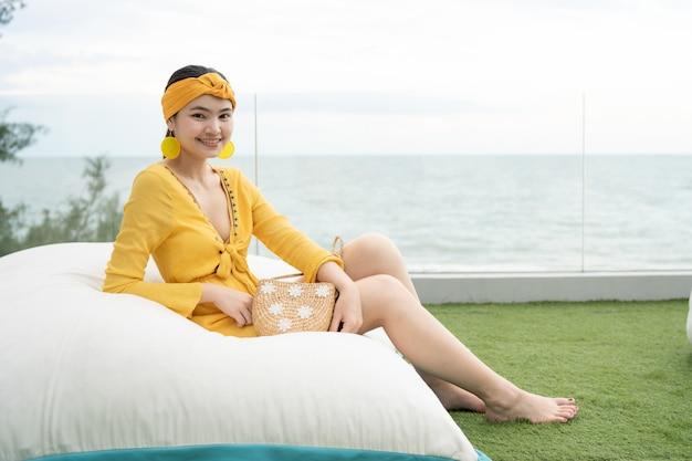 Schöne frau, die ein schönes gelbes kleid sitzt auf einem weichen kissen auf dem strand trägt