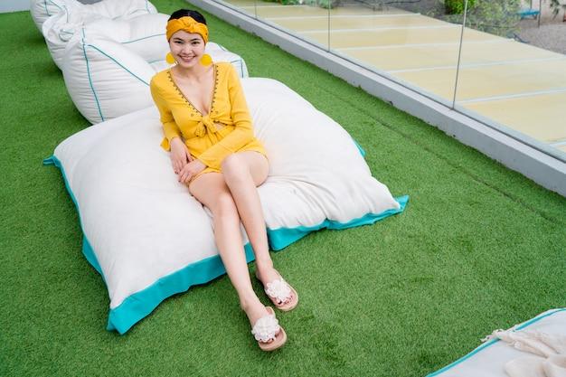 Schöne frau, die ein schönes gelbes kleid sitzt auf einem weichen kissen trägt