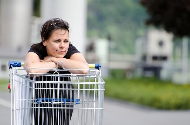 Schöne frau, die ein schwarzes hemd trägt, das sich auf einen einkaufswagen im parkplatz eines geschäfts stützt