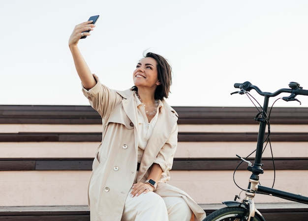 Schöne frau, die ein selfie draußen nimmt