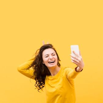 Schöne frau, die ein selfie mit kopienraum nimmt