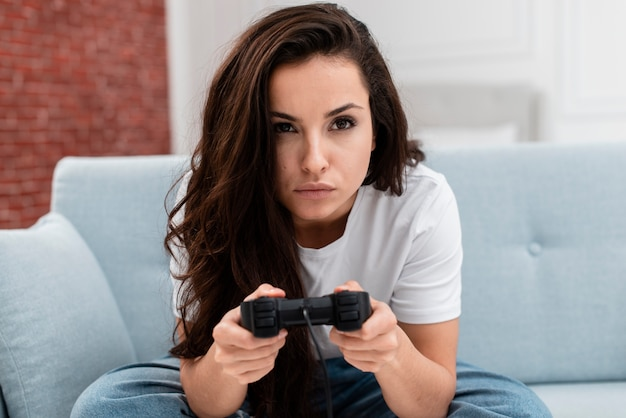 Schöne frau, die ein videospiel mit einem prüfer spielt