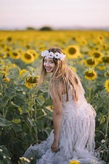Schöne frau, die ein weißes kleid trägt, lächelt und im sonnenblumenfeld steht