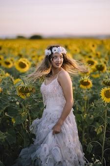 Schöne frau, die ein weißes kleid trägt und im sonnenblumenfeld steht standing