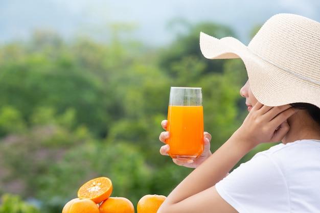 Schöne frau, die ein weißes t-shirt anhält ein glas orangensaft trägt