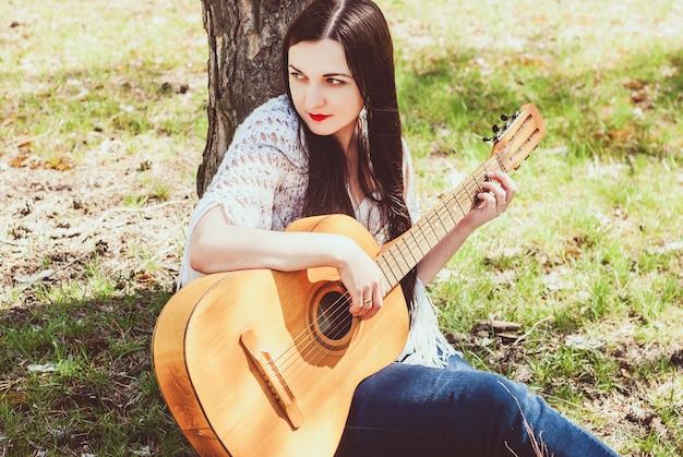 Schöne frau, die eine akustikgitarre im freien spielt