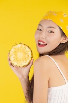 Schöne frau, die eine ananas anhält